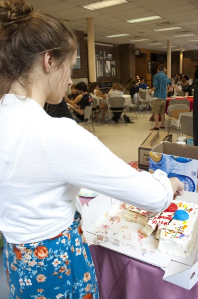 Sadie Birchfield (12) slices a piece of cake behind the food counter. | Photo by Meg Shanks