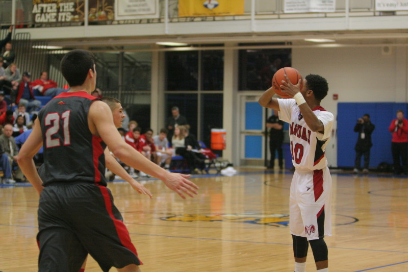 JaKory Freeman (12, #10) looks to pass the ball to a teammate as Bullet East players begin to close in on him.