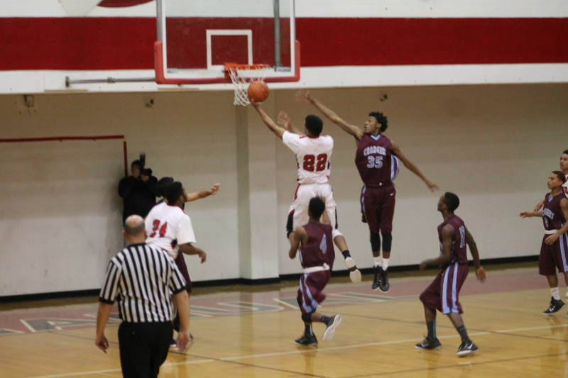 Dwayne Sutton (12, #22) rises for a layup over a Charger defender. Sutton leads all players in the Metro Louisville Area by averaging 24.2 ppg.