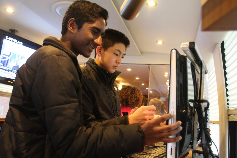 Madan Subheeswar (11) and Kevin Tien (11) interact with one of the many touchscreen computers on the bus.