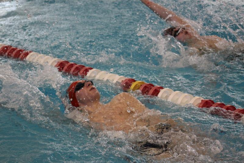 Graham Jolly (10) swims neck-in-neck with St. Francis swimmer Clayton Smedley. Smedley beat Jolly by a single second with a time of 33.04 seconds. Photo by Kate Hatter