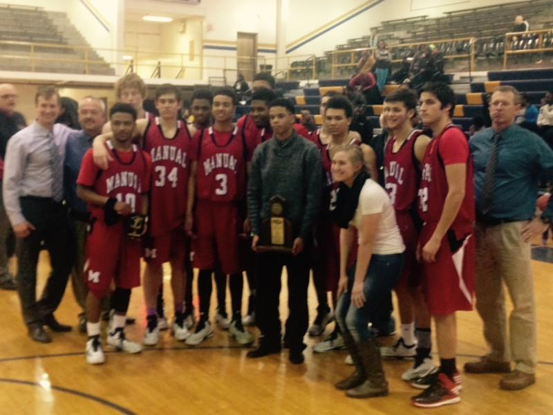 The Manual Boys Basketball team poses with the District 25 Tournament Championship Trophy after defeating Central. Photo by, Jack Grossman