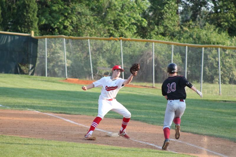 Sam Clinard (11, #22) tags out a Ballard runner attempting to reach first base in the second inning. Ballard did not have a single hit in the second inning.