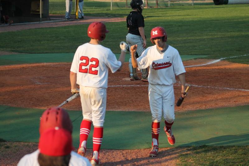Evan Dilbeck (11, #13) celebrates with teammate Sam Clinard (11, #22) after scoring off of a hit by Ben Cooper (12, #32). The score gave Manual its first lead of the game at 3-2.