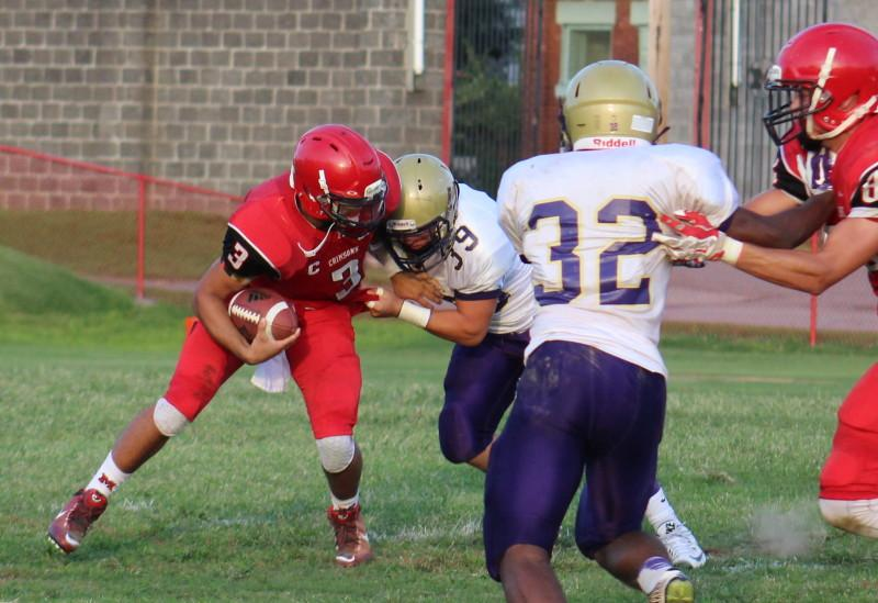Tim Comstock (12, #3) fights off a defender to try to avoid a sack. Photo by Kate Hatter