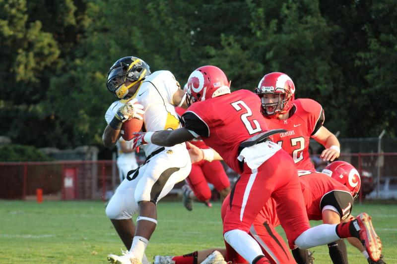 Omari Alexander (12, #2) forces a fumble. The Crimsons forced four turnovers in the game.