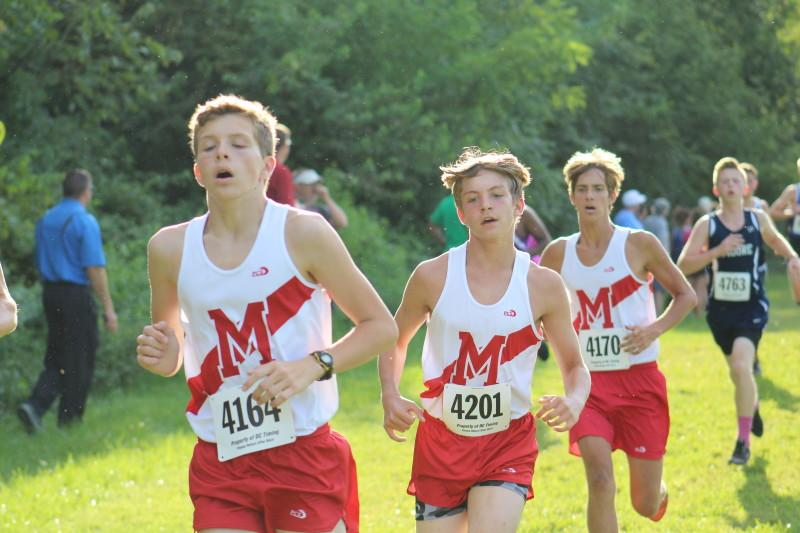 """Jackson Haile (11), Clayton Wagoner (10) and Graham Jolly (11) run down the last hill of the course to finish about half of their first mile. """"[When you are coming out of the woods down the first hill], the feeling is exhilarating. You feel like you can run for days,"""" Haile said. Photo by Kate Hatter"""