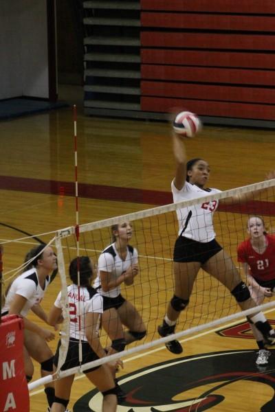 Tonysha Curry (12, #17) goes up to spike the ball.  Photo by Shea Dobson.
