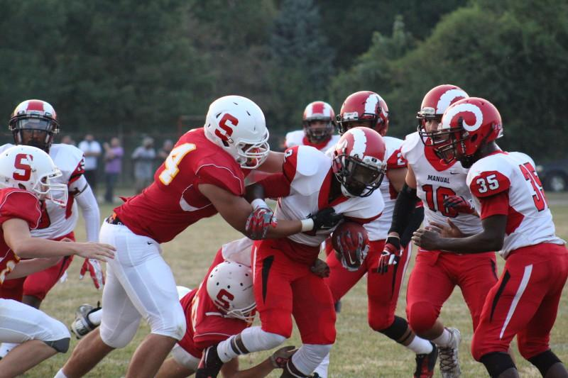 Omari Alexander (12, #2) fights Seneca defenders for a large gain for Manual offense. Photo by Kate Hatter