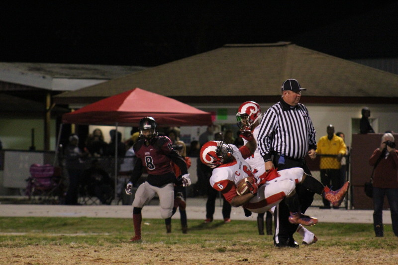 Andre Teague (11, #6) slips down to the ground in order to prevent himself from being tackled. Photo by Kate Hatter