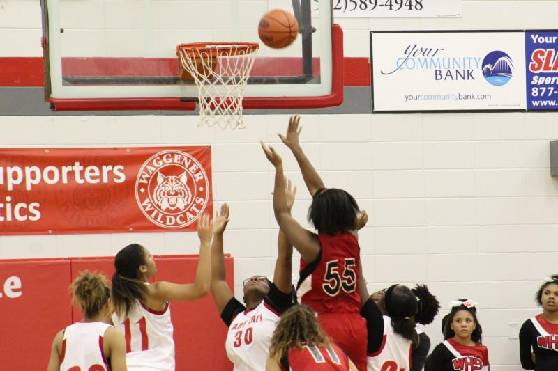 Krys McCune (12, #55) uses her height advantage to score over smaller Waggener defenders. Photo by Kate Hatter.