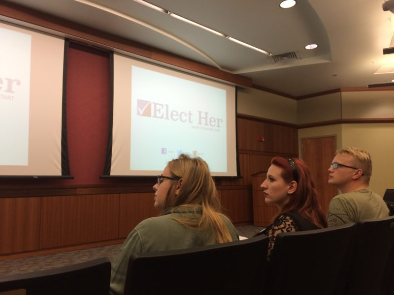 Audience members listen intently to Jessica Kelly present about women in politics.